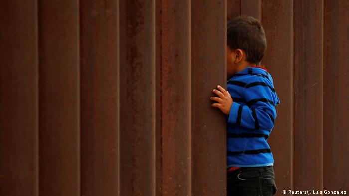 Criança próxima de muro na fronteira entre EUA e México