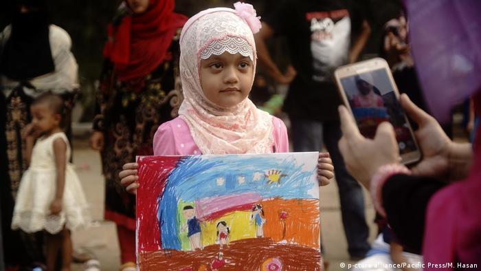 Una niña mostrando un cuadro.
