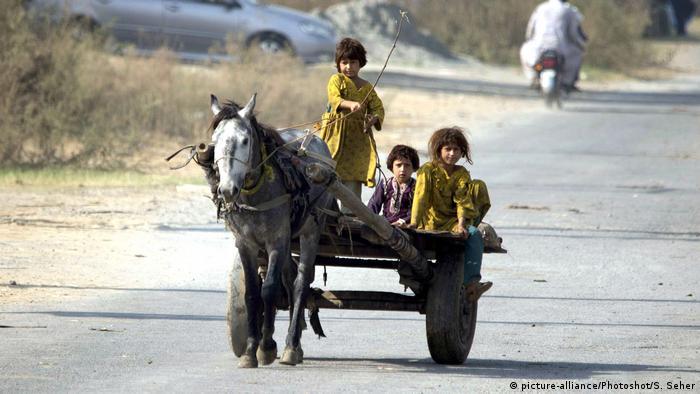 Meninas se divertem num passeio de carruagem no Paquistão