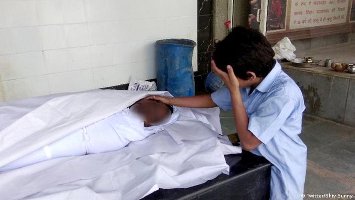 Niño llorando junto a su padre muerto.