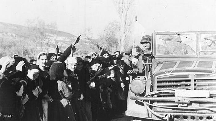 Greek villagers give the Nazi salute as German troops drive by in a vehicle