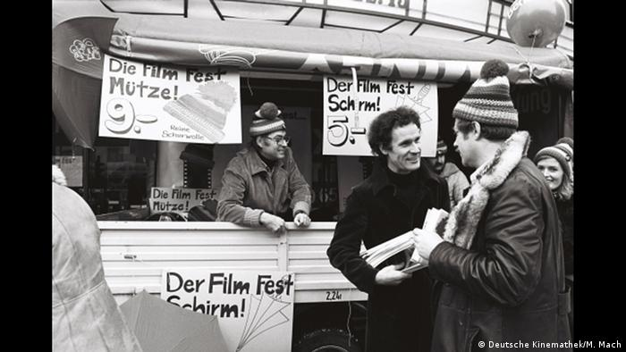 Wolf Donner in front of a Berlinale stand selling hats and umbrellas (Deutsche Kinemathek/M. Mach)