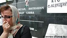 A woman weeps, standing at the memorial for killed journalists in the Chechen capital Grozny (?For journalists perished for the freedom of speech? is engraved on the wall and ?who is the next?? is written on the paper) as the portrait of journalist and human right activist Natalia Estemirova is placed on the wall, Russia 16 July 2009. Natalia Estemirova was abducted in Grozny on Wednesday and found dead in Ingushetia later on. EPA/KAZBEK VAKHAYEV +++(c) dpa - Bildfunk+++