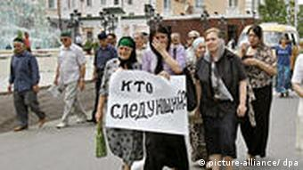 Women carry a sign during Estemirova's memorial service