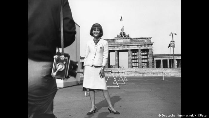 Claudia Cardinale and photographer in front of Brandenburg Gate and the Berlin Wall (Deutsche Kinemathek/H. Köster)
