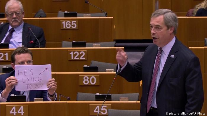 A man holding up a sign that reads He's lying to you while Nigel Farage addresses the European Parliament (picture-alliance/AP Photo)