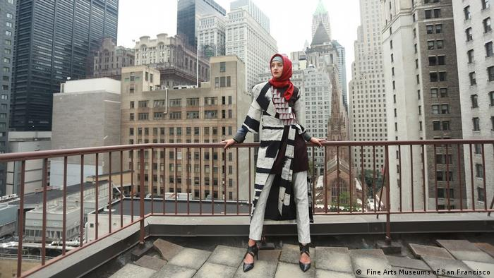 A woman in a black and white suit and jacket with a red headscarf stands on an urban balcony (Fine Arts Museums of San Francisco)