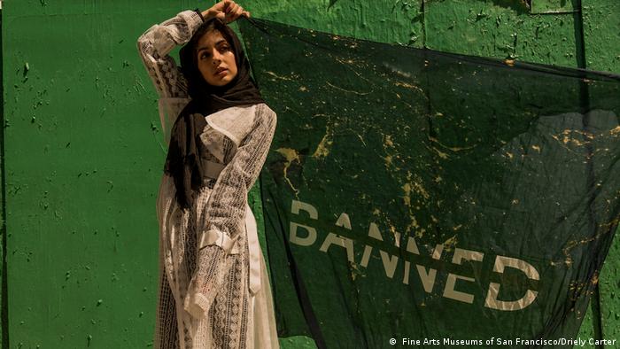 Das Model Hoda Katebi hält ein Tuch mit der Aufschrift banned hoch. (Fine Arts Museums of San Francisco/Driely Carter)