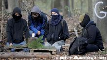 Masked activists mourn a fallen journalist in Hambach Forest