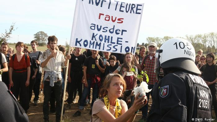 A policeman faces protesters at Hambach Forest