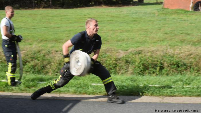 Firefighter rolling out hose (picture-alliance/dpa/S. Konjer)