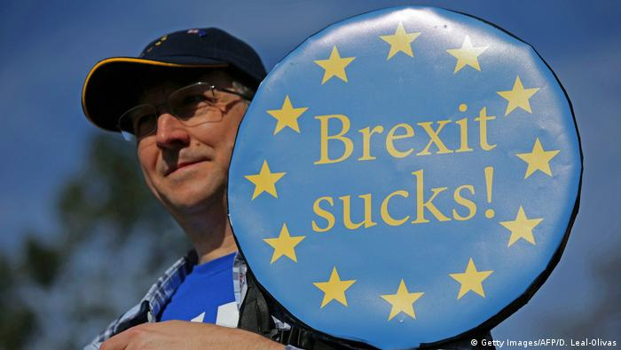 A protester holding a Brexit sucks sign