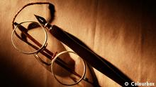 Old spectacles and ink pen on paper surface under beam of light