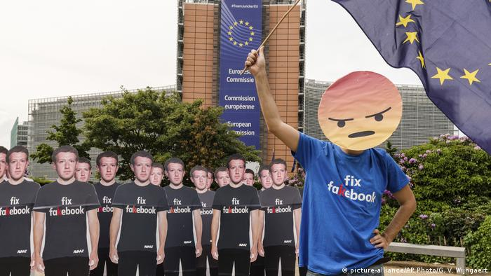 A person protesting against Facebook in Belgium holds an EU flag (picture-alliance/AP Photo/G. V. Wijngaert)