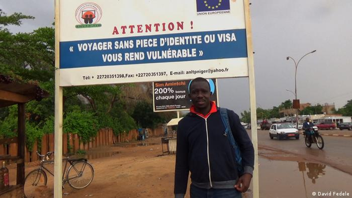 Kumut Imesh is standing in front of a big sign that reads in French: Attention! Voyager sans piece d'identite ou visa vous rend vulnérable