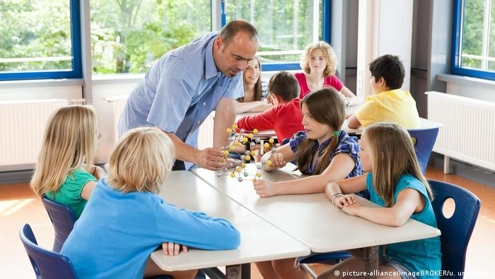 Teacher working with kids in a classroom (picture-alliance/imageBROKER/u. umstätter)