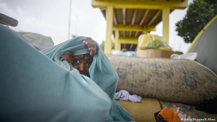 A child seeks shelter from the rain wrapped in a blanket, under the Ayrton Senna Viaduct in Manaus