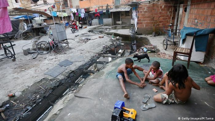 Crianças brincam no chão perto de um esgoto ao céu aberto numa favela no Rio de Janeiro