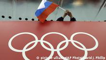FILE - In this Feb. 18, 2014, file photo, a Russian skating fan holds the country's national flag over the Olympic rings before the start of the men's 10,000-meter speedskating race at Adler Arena Skating Center during the 2014 Winter Olympics in Sochi, Russia. On Monday, July 18, 2016 WADA investigator Richard McLaren confirmed claims of state-run doping in Russia. (AP Photo/David J. Phillip, File) |