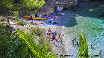 People swim and lie on the beach near clear blue water in Kefalonia (picture-alliance/N.Economou)