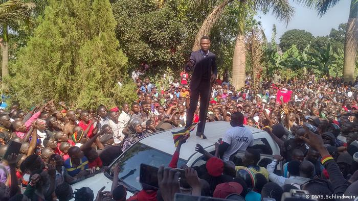Bobi Wine stands on the roof of a car giving a speech, surrounded by his supporters.