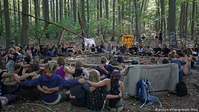 Activists and citizens sitting around an altar for the dead journalist in Hambach Forest