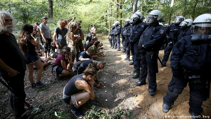 Activists light candles along a line of police in Hambach Forest