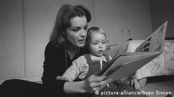 Mulher lendo livro com criança pequena