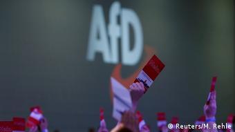 Рука с поднятым вверх партийным билетом АдГ