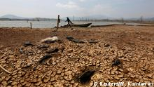 A fisherman walks to the waters edge in Jatigede Reservoir during the dry season in Sumedang, West Java, Indonesia, September 15, 2018. Picture taken September 15, 2018. REUTERS/Willy Kurniawan TPX IMAGES OF THE DAY