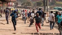 Protesters run for cover as they clash with eSwatini anti-riot police on September 19, 2018 in Manzini. - Undercurrents of dissent have surfaced this week with trade union protests over low wages by being broken up by riot police. At least 11 people were hurt on Tuesday, a trade union official told AFP. On Wednesday in the second city of Manzini, riot police and water canon trucks dispersed several hundred protesters, AFP reporters witnessed. (Photo by GIANLUIGI GUERCIA / AFP) (Photo credit should read GIANLUIGI GUERCIA/AFP/Getty Images)