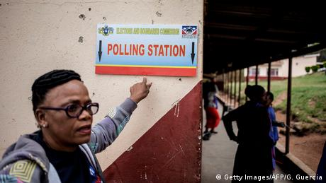 Woman in front of polling station sign (Getty Images/AFP/G. Guercia)