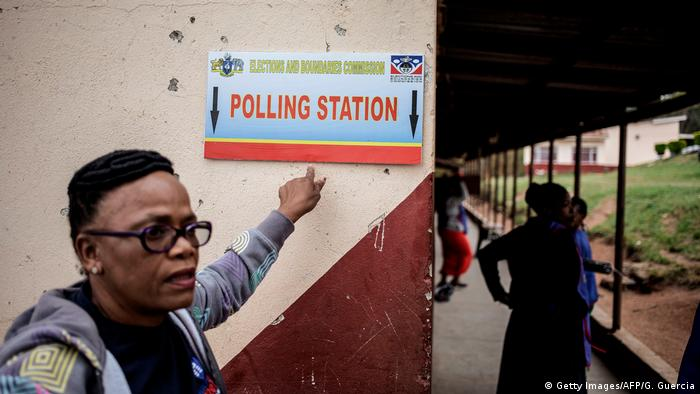 Woman in front of polling station sign