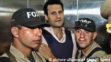 17.11.2003 FILE - In this Nov. 17, 2003 file photo, Lebanese citizen Assad Ahmad Barakat, who was then facing tax evasion charges, is escorted by police to a courthouse in Asuncion, Paraguay. On Friday, Sept. 21, 2018, federal police in Brazil arrested Barakat, a fugitive accused of belonging to Lebanon's Hezbollah militia and of being a key financier of terrorism. (AP Photo/Jorge Saenz, File) |