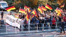 21.09.2018, Sachsen, Chemnitz: Teilnehmer einer Demonstration der rechtspopulistischen Bewegung Pro Chemnitz ziehen hinter Absperrgittern durch die Stadt. Sie tragen ein Transparent mit der Aufschrift Wir sind das Volk. Die Demonstration des rechtspopulistischen Bündnisses «Pro Chemnitz» und eine Gegendemo haben am Freitagabend zunächst weniger Menschen angezogen als in der Vorwoche. Foto: -/dpa-Zentralbild/dpa +++ dpa-Bildfunk +++ | Verwendung weltweit