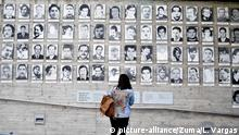 A woman looks at a wall of photographs showing victims of Chile's dictatorship