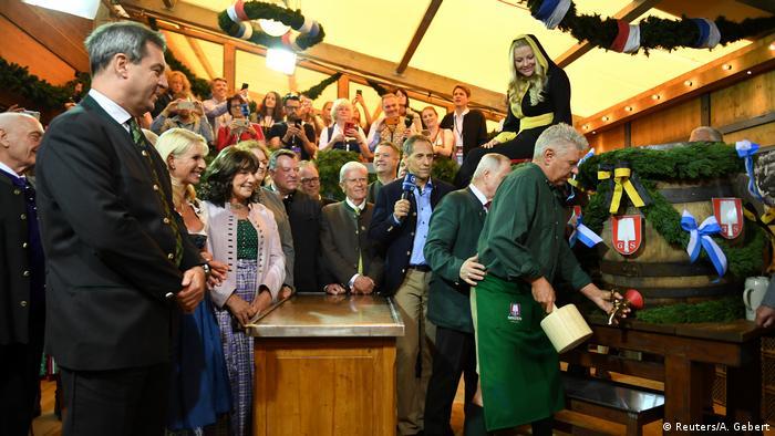 O prefeito de Munique, Dieter Reiter (dir.), abre o primeiro barril da festa observado pelo governador da Baviera, Markus Söder