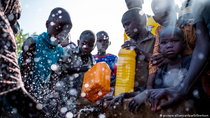 People in Nigeria fill up water bottles