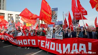 People hold up flags and banners and signs while protesting the pension reform (Reuters/M. Shemetov )