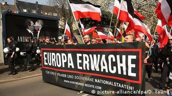 Membros de passeata extremista levam faixa negra em alemão e bandeiras