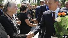 Local residents of Sukhumi, the capital of separatist Georgian region of Abkhazia, greet visiting Russian Prime Minister Vladimir Putin, right, Wednesday, Aug. 12, 2009. Putin said Wednesday his country will spend at least 15 billion rubles ($470 million) next year to build Russian military bases in Abkhazia and tighten it's borders. Then he traveled to Abkhazia's capital Sukhumi to meet officials of the separatist government. (AP Photo/RIA Novosti,Alexei Nikolsky, Pool)