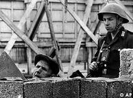 Soldado vigia trabalhador que faz reparos no Muro