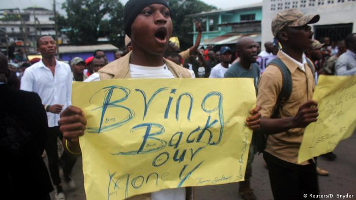 Liberia: A protester holding a sign that reads Bring Back Our Money (Reuters/D. Snyder)