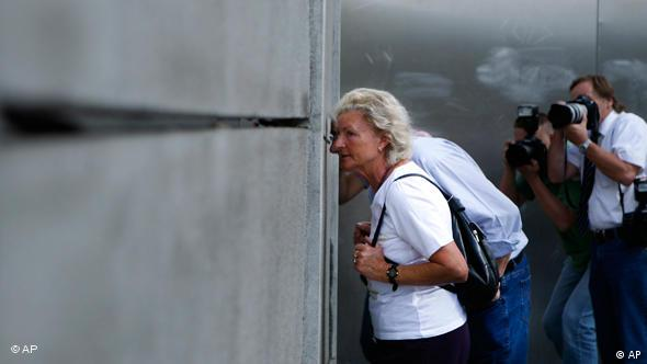 Female tourist looking through concrete slabs, which are part of the Wall Memorial in Berlin