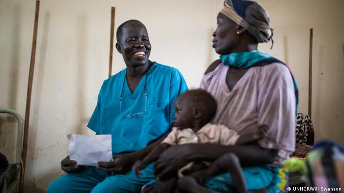 Dr Evan Atar Adaha, wearing surgeons scrubs, sits with a South Sudanese refugee and her young son at Maban hospital