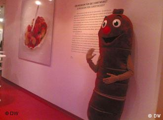 A life-sized currywurst mascot leans against a wall