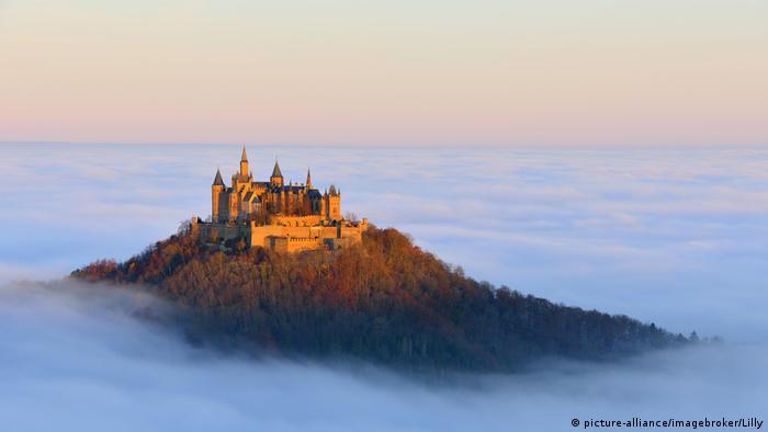 Auf einem Hügel wird ein mittelalterliches Burgensemble vom Morgenlicht erstrahlt, darum breitet sich eine Wolkendecke aus (Foto: picture-alliance/imagebroker/Lilly)