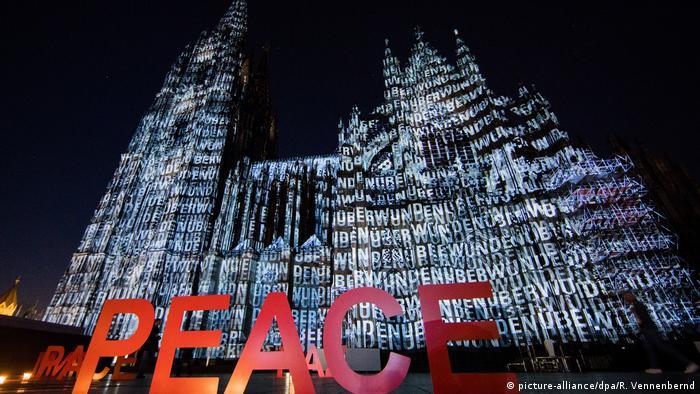 Große rote PEACE Buchstaben vor dem erleuchteten Dom, Deutschland Illumination am Kölner Dom (picture-alliance/dpa/R. Vennenbernd)