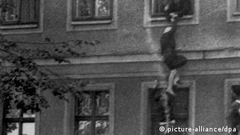 Женщина спускается из окна дома