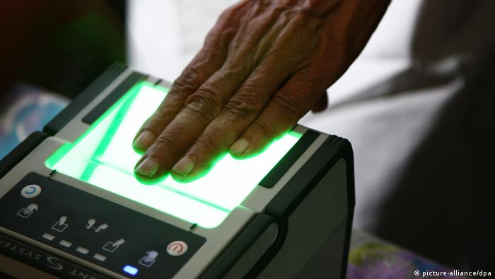 An Indian man scans his finger prints for Aadhaar ID enrollment